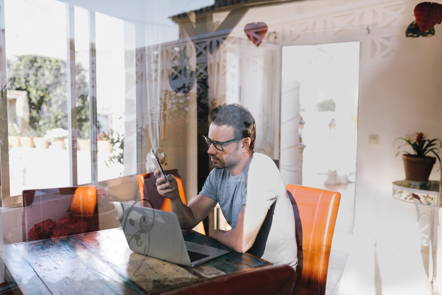 view of employee working from home through window